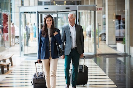 Business couple pulling suitcases in a hotel lobby Stock Photo - Premium Royalty-Free, Code: 6108-06905031