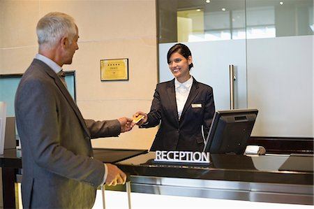 Businessman paying with a credit card at the hotel reception counter Stock Photo - Premium Royalty-Free, Code: 6108-06905034