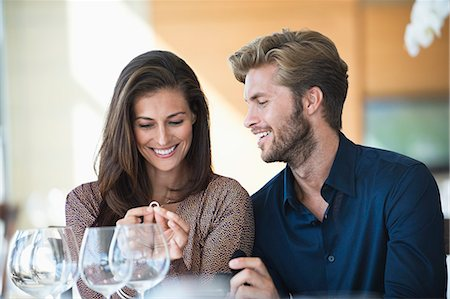Man giving engagement ring to his girlfriend in a restaurant Stock Photo - Premium Royalty-Free, Code: 6108-06905156