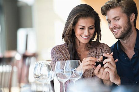 Man giving engagement ring to his girlfriend in a restaurant Stock Photo - Premium Royalty-Free, Code: 6108-06905172