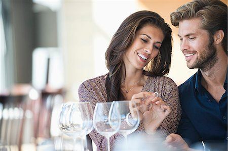 Man giving engagement ring to his girlfriend in a restaurant Stock Photo - Premium Royalty-Free, Code: 6108-06905177