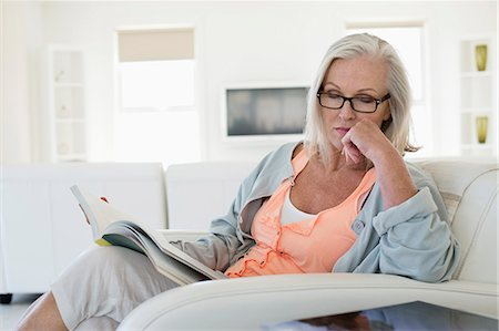 Woman sitting on a couch with holding a book and thinking Stock Photo - Premium Royalty-Free, Code: 6108-06905110