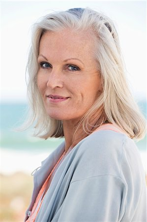 Portrait of a woman smiling on the beach Stock Photo - Premium Royalty-Free, Code: 6108-06905117