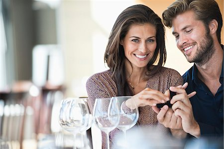 Man giving engagement ring to his girlfriend in a restaurant Stock Photo - Premium Royalty-Free, Code: 6108-06905139