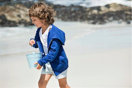 Boy playing on the beach Stock Photo - Premium Royalty-Free, Code: 6108-06905277
