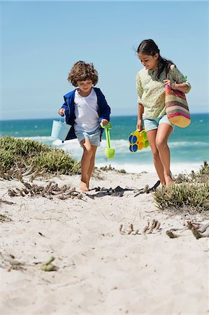 Girl and a boy walking on the beach Stock Photo - Premium Royalty-Free, Code: 6108-06905281