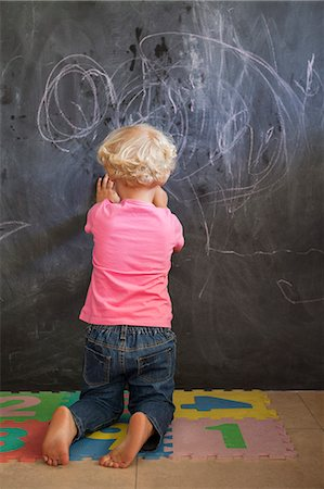 Rear view of a girl writing on a blackboard Stock Photo - Premium Royalty-Free, Code: 6108-06905284