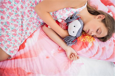 Girl sleeping on the bed with a rag doll Stock Photo - Premium Royalty-Free, Code: 6108-06905210