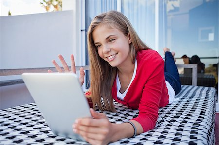 Girl lying on the bed and video chatting on a digital tablet Stock Photo - Premium Royalty-Free, Code: 6108-06905223