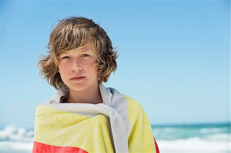 Portrait of a boy wrapped in a towel on the beach Stock Photo - Premium Royalty-Free, Code: 6108-06905220