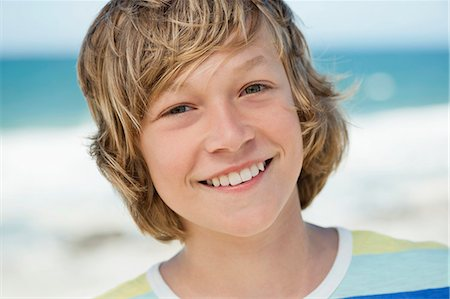 Portrait of a boy smiling on the beach Stock Photo - Premium Royalty-Free, Code: 6108-06905227