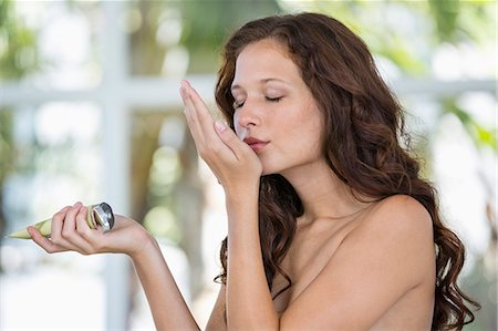 Woman smelling moisturizer Stock Photo - Premium Royalty-Free, Code: 6108-06905348