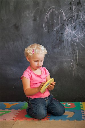 Girl playing with number puzzle in front of a black board Stock Photo - Premium Royalty-Free, Code: 6108-06905313