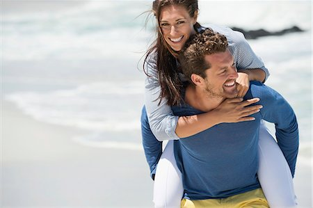 Man giving piggyback ride to his wife on the beach Stock Photo - Premium Royalty-Free, Code: 6108-06905490