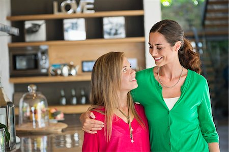 Woman smiling with her daughter at home Stock Photo - Premium Royalty-Free, Code: 6108-06905553