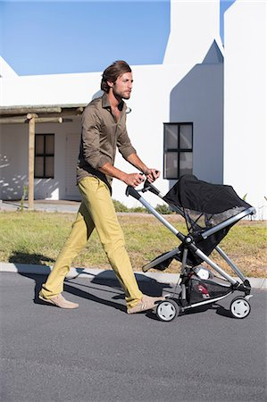 pushing - Man pushing a baby stroller on a road Stock Photo - Premium Royalty-Free, Code: 6108-06905582