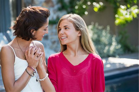 Close-up of a woman and her daughter smiling together Stock Photo - Premium Royalty-Free, Code: 6108-06905597