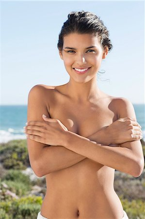 Topless woman covering her breasts with hands on the beach Stock Photo - Premium Royalty-Free, Code: 6108-06905512