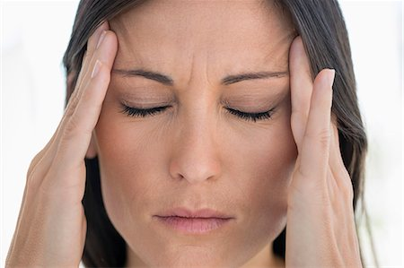 Close-up of a woman suffering from a headache Stock Photo - Premium Royalty-Free, Code: 6108-06905695