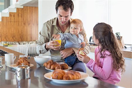 sister - Family having breakfast at a kitchen counter Stock Photo - Premium Royalty-Free, Code: 6108-06905618