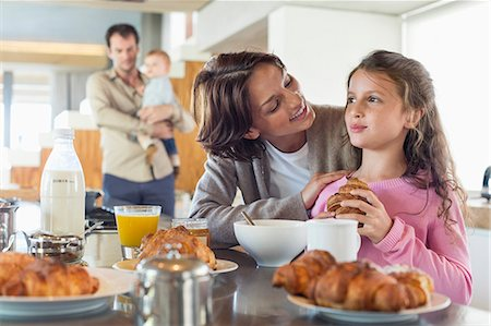 sister - Girl having breakfast beside her mother at a kitchen counter Stock Photo - Premium Royalty-Free, Code: 6108-06905749