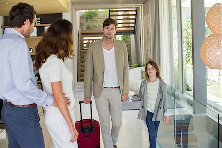 Man with his daughter arriving at his friends home from holiday Stock Photo - Premium Royalty-Free, Code: 6108-06905750