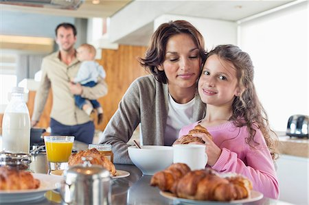 Girl having breakfast beside her mother at a kitchen counter Stock Photo - Premium Royalty-Free, Code: 6108-06905758