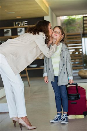 daughter kissing mother - Woman kissing her daughter arriving from holiday Stock Photo - Premium Royalty-Free, Code: 6108-06905759