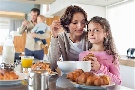 Girl having breakfast beside her mother at a kitchen counter Stock Photo - Premium Royalty-Free, Code: 6108-06905763