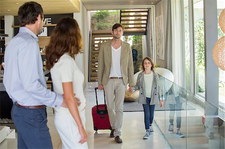 Man with his daughter arriving at his friends home from holiday Stock Photo - Premium Royalty-Free, Code: 6108-06905767