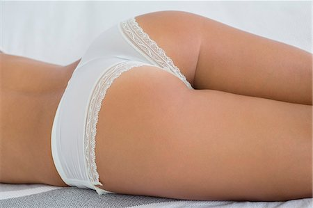 Mid section view of a woman lying on the bed in lingerie Stock Photo - Premium Royalty-Free, Code: 6108-06905778