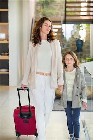 Woman walking with her daughter with a luggage Stock Photo - Premium Royalty-Free, Code: 6108-06905731