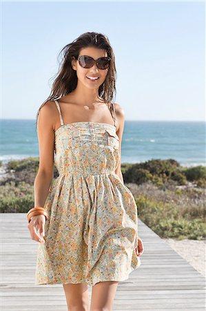Beautiful woman walking on a boardwalk Stock Photo - Premium Royalty-Free, Code: 6108-06905856