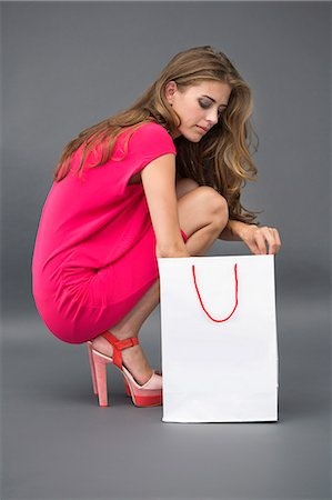 Woman searching into a shopping bag Stock Photo - Premium Royalty-Free, Code: 6108-06905881