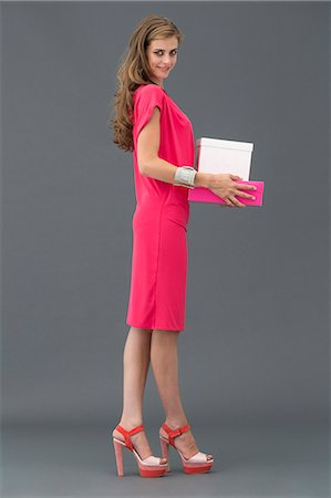 Portrait of a woman carrying boxes and smiling Stock Photo - Premium Royalty-Free, Code: 6108-06905889
