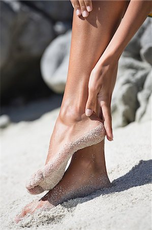 female feet close up - Woman cleaning sand of her feet Stock Photo - Premium Royalty-Free, Code: 6108-06905800
