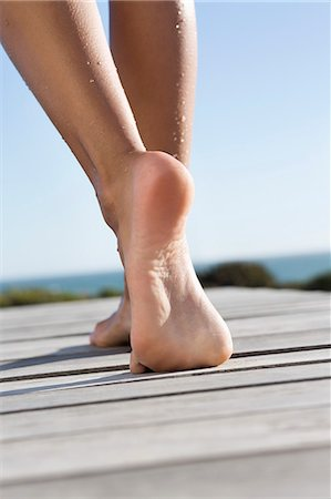 female feet close up - Low section view of a woman walking on boardwalk on the beach Stock Photo - Premium Royalty-Free, Code: 6108-06905801
