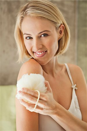 Beautiful smiling woman cleaning with a bath sponge Stock Photo - Premium Royalty-Free, Code: 6108-06905814