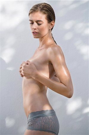 Woman hiding her breast with her hands Stock Photo - Premium Royalty-Free, Code: 6108-06905831