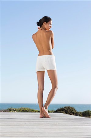 Rear view of a topless woman standing on the beach Stock Photo - Premium Royalty-Free, Code: 6108-06905834