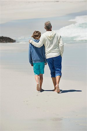 Man walking with his grandson on the beach Stock Photo - Premium Royalty-Free, Code: 6108-06905942