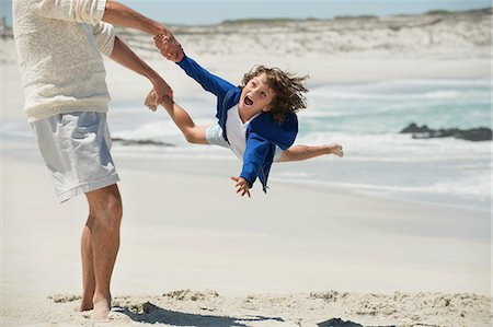 Man playing with his grandson on the beach Stock Photo - Premium Royalty-Free, Code: 6108-06905946
