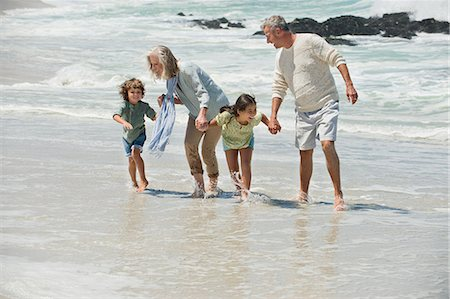 Children walking with their grandparents on the beach Stock Photo - Premium Royalty-Free, Code: 6108-06905949