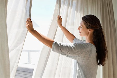 Woman opening the curtain of a window Stock Photo - Premium Royalty-Free, Code: 6108-06905957
