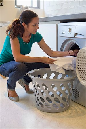 Woman doing laundry at home Stock Photo - Premium Royalty-Free, Code: 6108-06905959