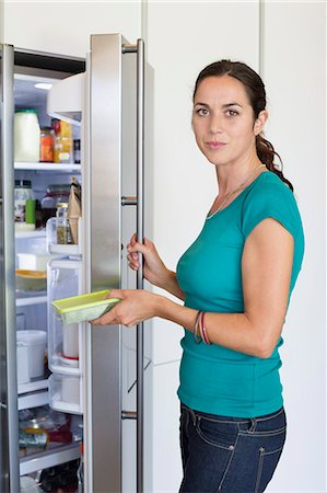 Woman putting food in a refrigerator Stock Photo - Premium Royalty-Free, Code: 6108-06905965