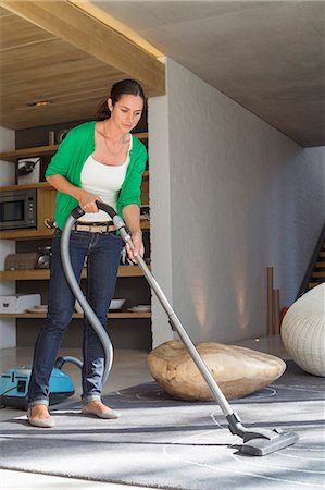 Woman cleaning house with a vacuum cleaner Stock Photo - Premium Royalty-Free, Code: 6108-06905975