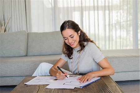 Woman doing paperwork at home Stock Photo - Premium Royalty-Free, Code: 6108-06905982