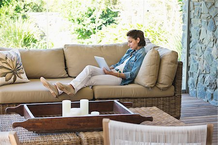 property release - Woman reclining on a couch and using a digital tablet Stock Photo - Premium Royalty-Free, Code: 6108-06905991