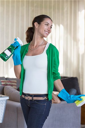 Woman holding cleaning equipment and smiling Stock Photo - Premium Royalty-Free, Code: 6108-06905996
